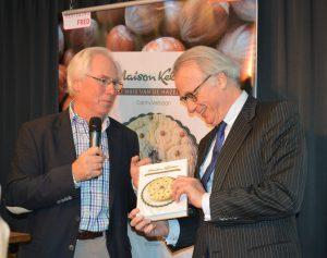 Burgemeester Van Aartsen (rechts) ontvangt het eerste exemplaar van het boek met de geschiedenis van banketbedrijf Maison Kelder. Oud-eigenaar Lucas Jonker (links) trad op als opdrachtgever.